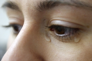 Image of a lady crying to illustrate domestic abuse.