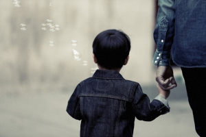 Image of child blowing bubbles and holding a parents hand to illustrate how fostercare can benefit you.
