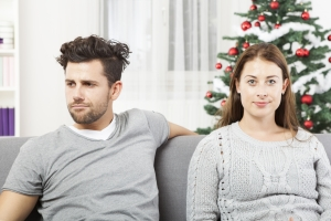 An image of a couple being irritated with each other on a sofa, used to illustrate being divorced & living together at christmas.